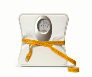 Scale Showing Lost Weight With Tightened Tape Measure